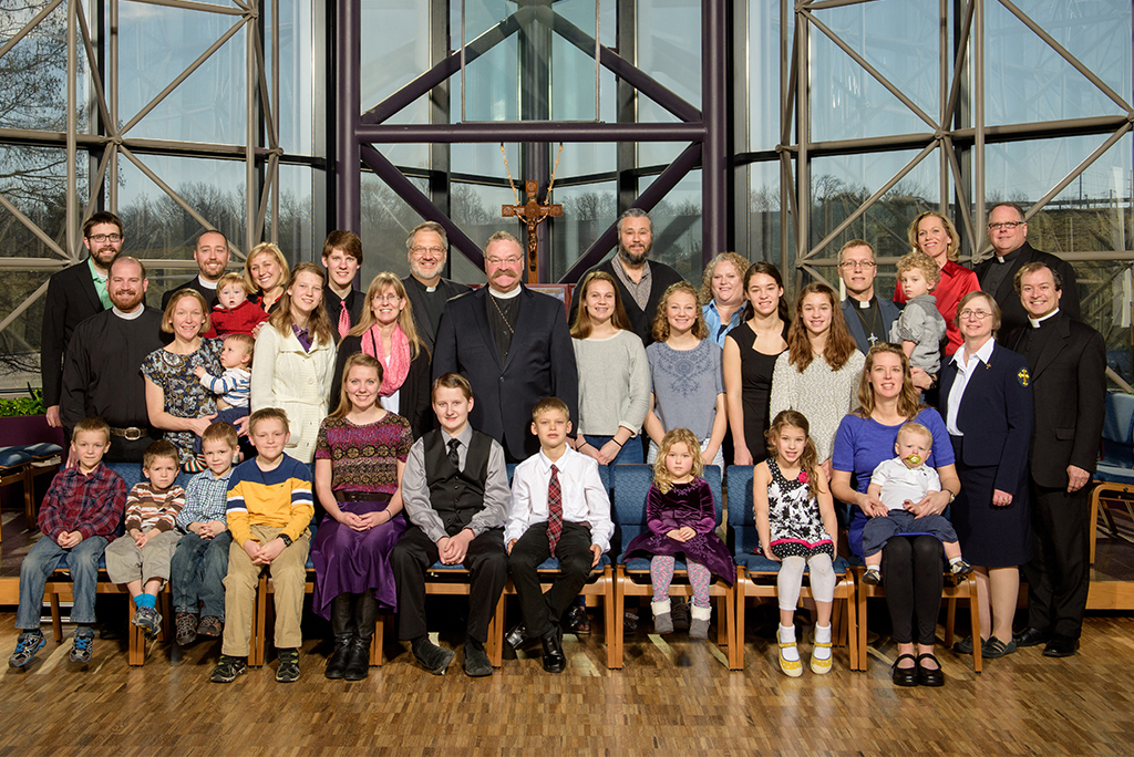 New missionaries and their families pose for a group photo at the start of the winter 2016 orientation, Feb. 29-March 11 in St. Louis, along with LCMS President Rev. Dr. Matthew C. Harrison (in center, just left of cross). (LCMS/Erik M. Lunsford)