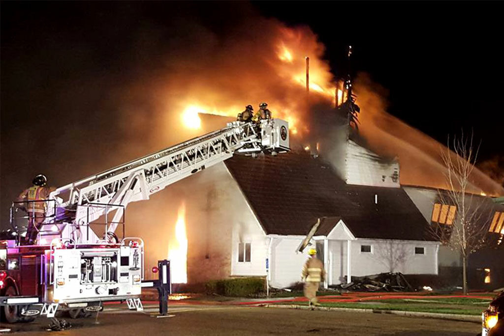 Firefighters work to bring flames under control March 30 at St. James Evangelical Lutheran Church in Northrop, Minn. Fire crews from five towns responded to the overnight fire, which was started by lightning, according to authorities. (Courtesy of The Truman Tribune)