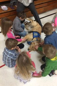 """Preschoolers gather around """"Lizzie,"""" a K-9 Comfort Dog (in training) from Lutheran Church Charities, after an April 3 worship service at Martin Luther High School in Northrop, Minn. The service was the first for members of St. James Evangelical Lutheran Church, Northrop, since a March 30 fire destroyed the church building. (Lutheran Church Charities)"""