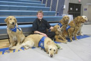 """The Rev. Robert C. Trueblood, pastor of St. James Evangelical Lutheran Church in Northrop, Minn., poses with six of the 10 """"comfort dogs"""" from Lutheran Church Charities that visited the town after fire destroyed the church building. (Elaine Tessler/Immanuel Lutheran Church, Belvidere, Ill.)"""