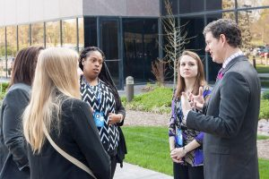Awaiting their turn to present, Concordia University Chicago students, from left, Ellen Moussou (partially hidden), Elisabeth Desiron, Jasmin Drake and Jodi Ulm confer with Daniel Stiller, assistant professor of marketing and the team's faculty advisr. (LCEF/Jay T Garrott)