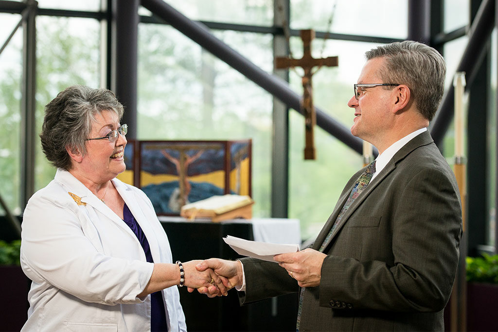 Sally Handrick, chairman of the Lutheran Women's Missionary League's Mission Grants Committee, presents LCMS Chief Mission Officer Rev. Kevin Robson with a check for an LWML grant to LCMS Disaster Response. The grant will help more than 20 LCMS congregations purchase and outfit disaster-response trailers. (LCMS/Erik M. Lunsford)