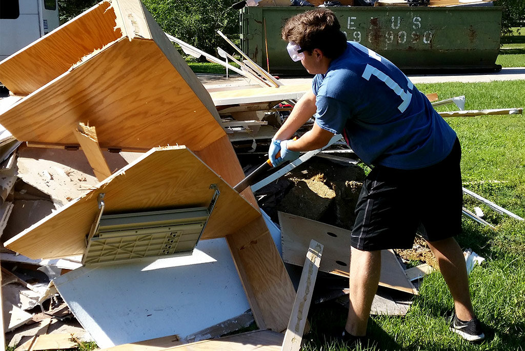A youth member of St. Timothy Lutheran Church in Houston assists with flood cleanup in Cypress, Texas, by breaking up debris at a local Bethesda Lutheran Communities group home April 21. (Melisa May)