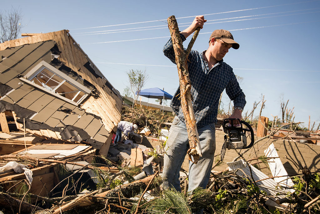 """John Gorman removes debris from a tornado-destroyed home in Tupelo, Miss., on May 2, 2014. """"LCMS Camp Courage: A Place of Hope and Healing"""" — a weeklong vacation Bible school program designed to help traumatized children rebound from disasters — is the Synod's latest """"crowdfunding"""" project. Its goal is to raise a total of $6,430 by June 14. (LCMS/Erik M. Lunsford)"""