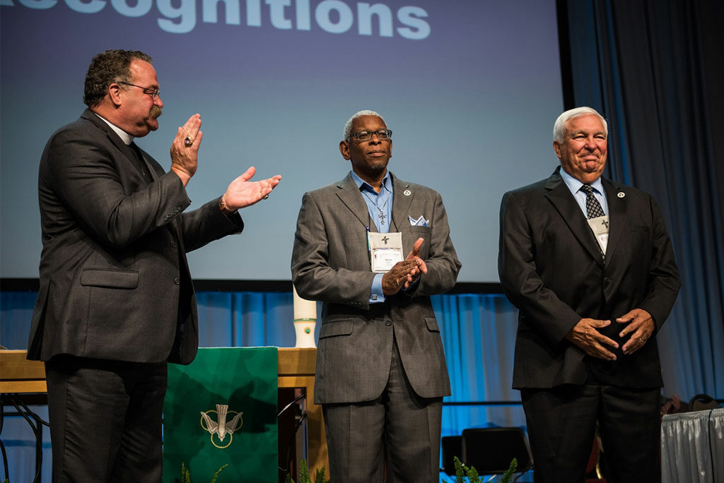 LCMS President Rev. Dr. Matthew C. Harrison helps recognize outgoing Synod Board of Directors members Rev. Dr. Victor Belton, center, and Warren Puck, right, on Tuesday, July 12. During the presentation of Floor Committee 7, Concordia University System, on Thursday, July 14, Belton expressed thanks to the assembly for past and ongoing support of Concordia College Alabama, Selma. (LCMS/Frank Kohn)