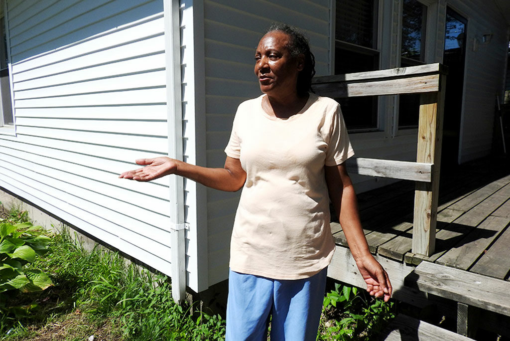 Betty Harris shows off the new siding on her East St. Louis home, made possible by a Lutheran Housing Support initiative that provides resources to congregations and community partners to assist low-income, disabled or elderly homeowners. (LCMS/Joe Isenhower Jr.)