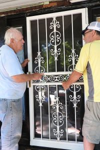 Bob Bohnhoff, left, and Joe Feigl install a new door at one of the nine homes in East St. Louis, Ill., where LCEF's Laborers For Christ is working for Unity Lutheran Church and Lutheran Housing Support as part of the Helping Hand Initiative. (LCMS/Joe Isenhower Jr.)