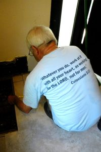 """Ron Horstmann adds tile to an East St. Louis home wearing his Laborers For Christ T-shirt with a meaningful Bible verse. Horstmann calls the LCEF ministry """"our way to serve the Lord."""" (LCMS/Joe Isenhower Jr.)"""