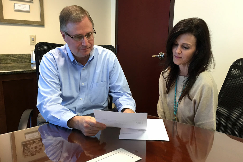 """The LCMS Florida-Georgia District is saving $2,000 in annual fees since moving from a commercial bank to the Lutheran Federal Credit Union, says district Business Manager John Elliott, going over paperwork with bookkeeper Laura Zirbel. He calls the savings """"money we can now use for the district's mission to serve, assist and encourage congregations in the ministry of Jesus Christ."""" (LCMS Florida-Georgia District)"""