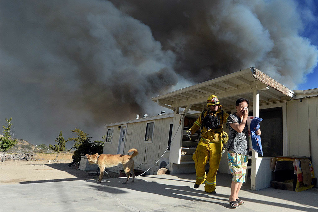 Firefighter Jeremy Pendergraft helps a woman out of her home as a wildfire off of Hwy. 138 approaches Aug. 16 in San Bernardino, Calif. (Will Lester/The Inland Valley Daily Bulletin via AP)