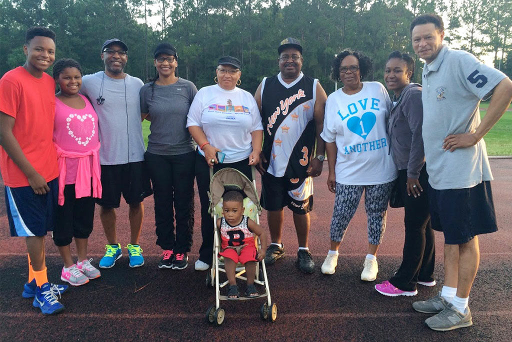 """The Rev. James Wiggins Jr. and his wife, Loretta (third and fourth from left), pose with other """"Walk with the Pastor"""" participants in July on the track at Florida State College of Jacksonville (Fla.). Wiggins, pastor of St. Paul Lutheran Church, Jacksonville, says he enjoys the fellowship of the early-morning walks. """"It's really a great time to not only get to know your members and leaders better, but it also allows you to meet other citizens from the community,"""" he told Reporter. (Courtesy of James Wiggins Jr.)"""