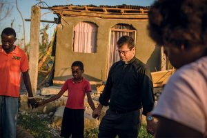 The Rev. Ross Johnson, director of LCMS Disaster Response, prays with a family outside a home severely damaged by Hurricane Matthew on Oct. 12 in a rural area of Les Cayes, Haiti. LCMS Disaster Response has provided, to date, $20,000 for 120,000 meals for people in the country's hardest-hit areas. (LCMS/Erik M. Lunsford)