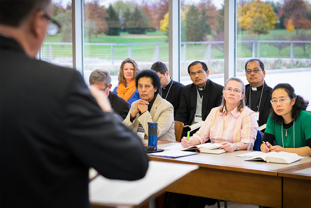 """The Rev. Dr. Jon Vieker, left, traces textual strands of LCMS hymnody for international attendees of the """"Fresh Hymns of Thankful Praise Arise"""" symposium at Concordia Theological Seminary in Fort Wayne, Ind. (LCMS/Michael Schuermann)"""