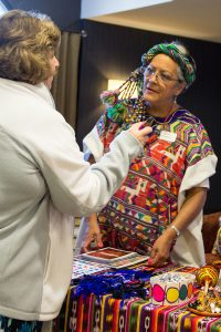 Rebeca de Franco, right, director of Lutheran Hour Ministry's ministry center in Guatemala City, Guatemala, talks about her work with a visitor to the International Village during the 100th-anniversary celebration in St. Louis. (©2016 Lutheran Hour Ministries)