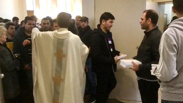 Copies of the new Luther's Small Catechism in Farsi are distributed as the Rev. Gottfreid Martens (in the clerical vestment) greets parishioners at Trinity Evangelical Lutheran Church in Berlin. (Lutheran Heritage Foundation)