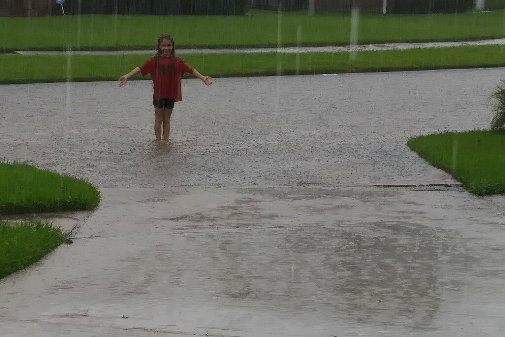 The author's daughter, Brooke, stands in the rain outside her home on Sunday, August 27. Photo credit: Jennifer Davis