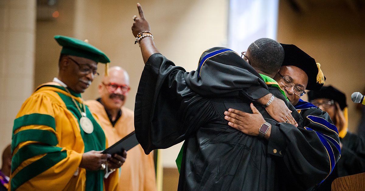 Dr. Glenn King Jr., dean of Business and Computer Information Systems at Concordia College Alabama, hugs a graduate during the commencement ceremony on Saturday, April 28, in Selma, Ala. (LCMS/Erik M. Lunsford)