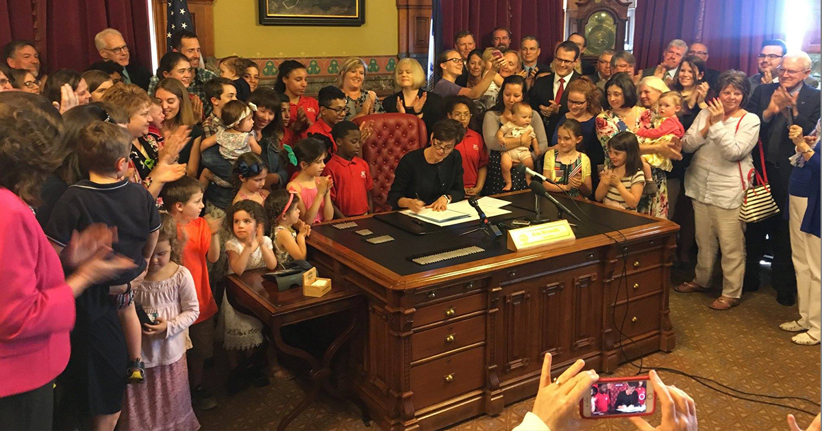 Iowa Governor Kim Richards signs the Iowa fetal heartbeat bill on May 4 as supporters of the legislation watch. Members of LCMS churches and organizations in Iowa were deeply involved in the bill's passage. (Kim Laube)