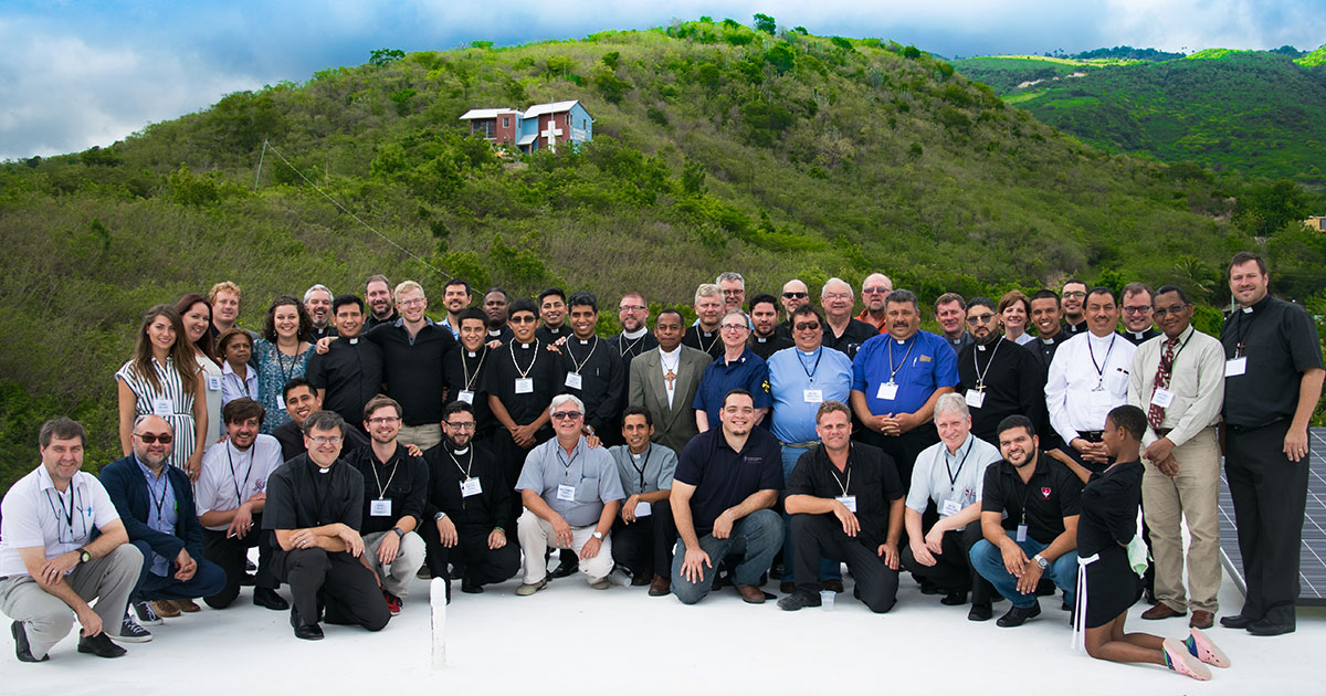 Attendees at the Heidelberg Symposium, held April 24–26 in Santiago, Dominican Republic, pose for a group photo on the white roof of the Concordia The Reformer Mercy Center and Seminary. The seminary dormitory is pictured in the background. (Jana Inglehart)