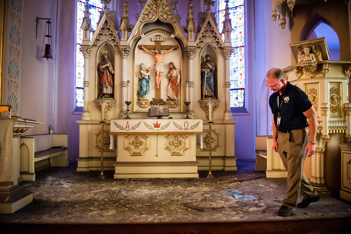 The Rev. Scott Schmieding, senior pastor at Immanuel Lutheran Church, St. Charles, Mo., surveys the church's altar on Monday, June 4, 2018. The entire baptismal side of the sanctuary's interior ceiling collapsed May 29 at 1.29 a.m. No one was injured in the collapse, and the altar was undamaged. (LCMS/Erik M. Lunsford)