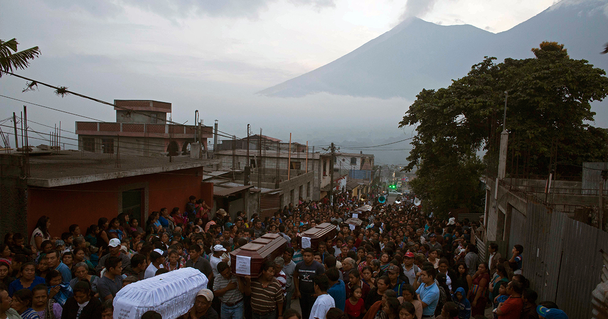Coffins containing the bodies of volcano victims are carried to the cemetery in San Juan Alotenango, Guatemala, on Monday, June 4. Residents of villages skirting Volcan de Fuego, seen in the background, began mourning the dead after an eruption buried them in searing ash and mud.